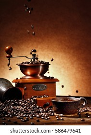 still life with coffee beans and clay cup and turk on. Cofffee beams pouring into old coffee mill(motion effect) and turk on the wooden background.