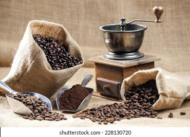 still life of coffee beans in jute bags with coffee grinder