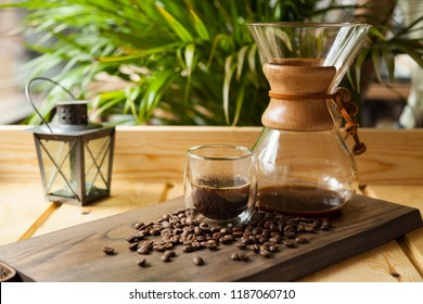 Still life with coffee in a chemex jar with coffee inside and a cup of glass with beans spilled around the glass on a wooden table on a coffee shop environment with a small lamp. Coffee concept