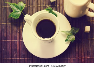 still life with coffee Cup and milkman on brown background.