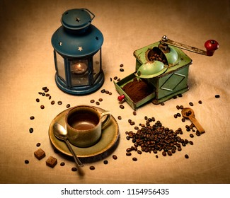 Still life with coffee mill cup spoon sugar ground and unground coffee beans and candle lamp