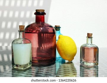 Still life with cold fresh lemonade, compote and lemon juice in the small vintage glass botlles against a high key background with space for your text. Selective and soft focus.