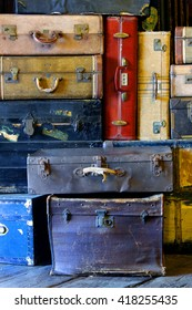 Still life of colorful worn out antique suitcases.