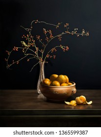 Still life composed of Asiatic bittersweet branches with fruit, vase, bowl of clementines.