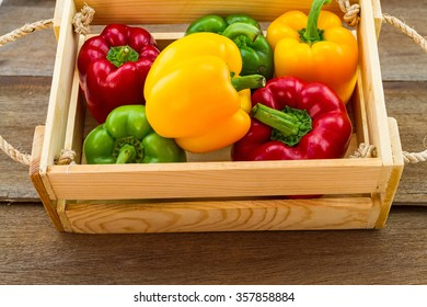still - life concept colorful of fresh  sweet bell pepper (capsicum)   in wooden basket on wooden background