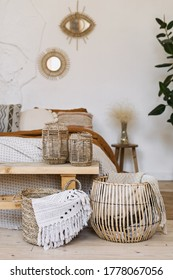 Still life concept. Vertical photo of cozy apartment in boho chic style interior with comfort bedroom, fabric sheet plaid on bed, wooden bench seat, dry plants in vase, home decor in wicker basket