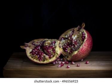 Still life of cool pomegranates on black dark background