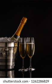 Still life with cooled champagne bottle standing in a bucket with ice and two full champagne flutes on a black background with reflection