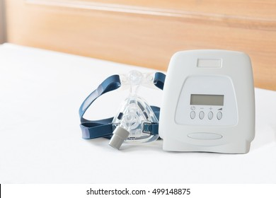 Still life of Cpap machine and mask on white bed sheet in the morning light. CPAP machine components.