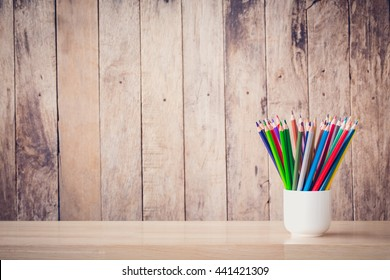 Still life with crayon or pastel Pencil in a glass of white on a wooden floor for background. picture used for add text or education message.