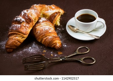 Still life with cup of fresh coffee and delicious butter croissants on dark brown board