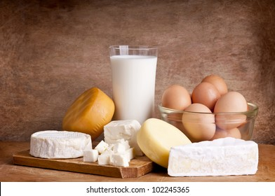 still life with dairy products, milk, cheese and eggs on a wooden background