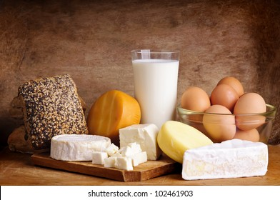 still life with dairy products, milk, eggs, bread and cheese on a vintage wooden background