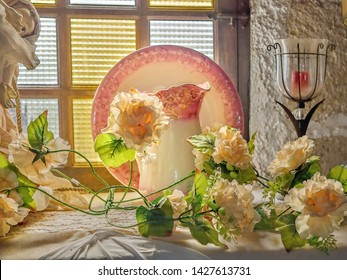 Still life with delicate yellow roses, glass candlesticks, an old upstanding plate with pink flower border, in front of it a matching water carafe in Art Nouveau style. Behind is a window