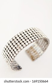 Still life detail view of a luxury quality diamond bracelet isolated against a white background. Sparkling jewelry fashion accessory, interior view.