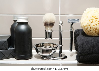Still life detail view of a man exclusive grooming and shaving kit in a luxury home or hotel bathroom with soaps and gels, towels and a sponge. Home interior view.