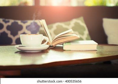 Still life details, cup of coffee with book on wood table