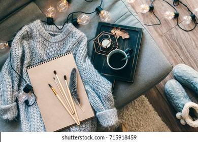 Still life details. Cup of coffee on rustic wooden tray, sketchbook and warm woolen sweater on sofa, decorated with led lights, top view point. Autumn weekend concept. Hobby and crafts.