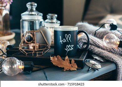 Still life details of living room. Cup of coffee on rustic wooden tray, candle and warm woolen sweater on table, decorated with led lights. Autumn weekend concept. Fall home decoration.