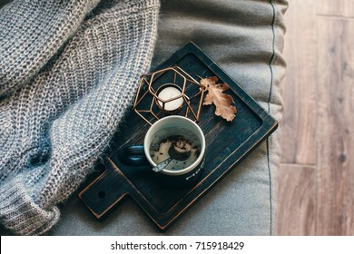 Still life details of living room. A cup of coffee on the rustic wooden tray, candle and warm woolen sweater on the sofa, top view point. Autumn weekend concept. Fall home decoration.
