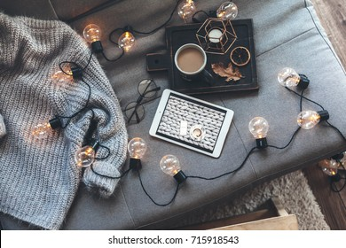 Still life details of living room. Cup of coffee on rustic wooden tray, tablet and warm woolen sweater on sofa, decorated with led lights, top view point. Autumn weekend concept. Watching movie.