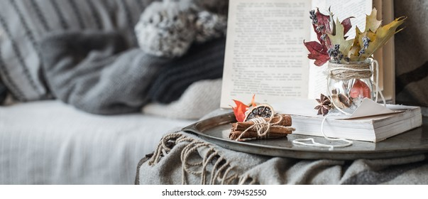 The still life details in the living room. Autumn composition on the background of cozy sofas and sweaters, the concept of leisure and autumn weekends