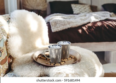 Still life details of nordic interior. Two cups of cocoa with marshmallows on wooden tray on a armchair with sheep fur cover in bedroom. Lazy winter morning in log cabin.