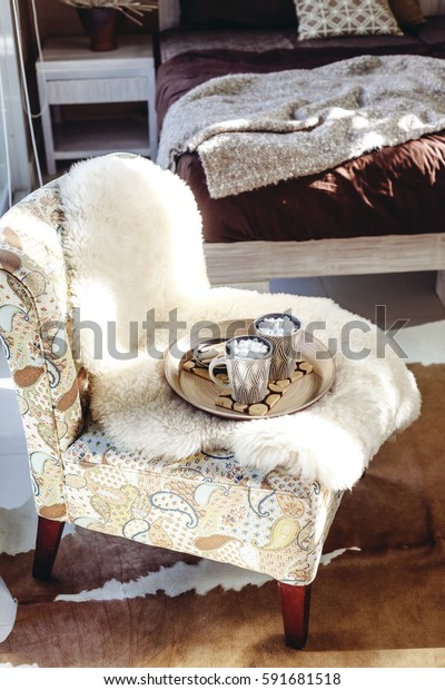 Still life details of nordic interior. Two cups of cocoa with marshmallows on wooden tray on a armchair with sheep fur cover in bedroom, cow skin carpet on the floor. Lazy winter morning in log cabin.