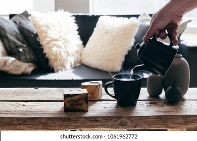Still life details of nordic living room. Pouring tea with steam on a rustic coffee table over black sofa in morning sunlight. Cozy winter concept in scandinavian home interior.