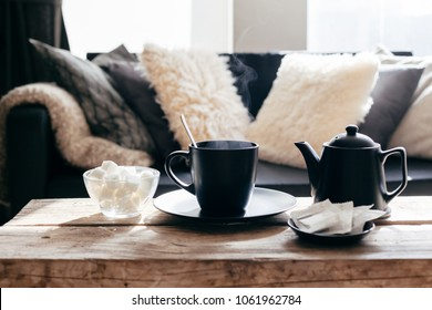 Still life details of nordic living room. Cup of hot tea with steam on a rustic coffee table over black sofa in morning sunlight. Cozy winter concept in scandinavian home interior.