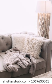 Still life details of nordic living room. Warm sweater on the sofa with fur cushions. Cozy winter scene in Scandinavian interior.