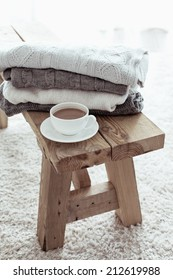Still life details, stack of winter sweaters on rustic bench on white carpet