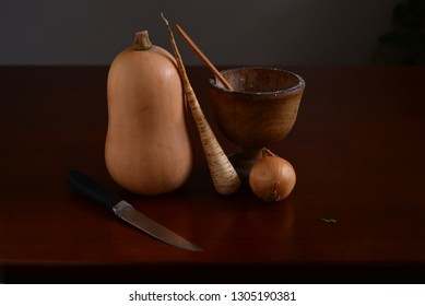 Still life in dim light condition with vegetables and knife.