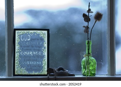 Still life of dried decorative reeds in green glass bottle, and serenity prayer glass panel in window, with snow storm behind.