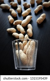 Still life with dried peanuts in their nutshells and small vintage glass against a low key background. Choose a focal point.