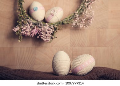 Still life Easter background with Easter eggs and flower wreath, pastel colours decoration from rope, ribbon with wooden background