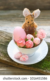 Still Life with Easter bunny, rose and colorful eggs in Cup on light background. Easter still life. soft selective focus.