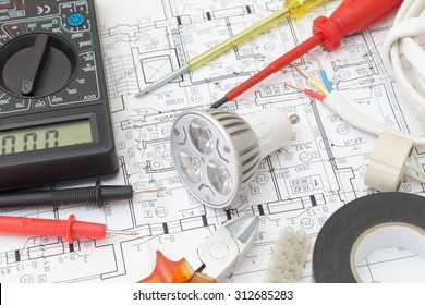 Still Life Of Electrical Components Arranged On Plans. Centered on a light bulb.