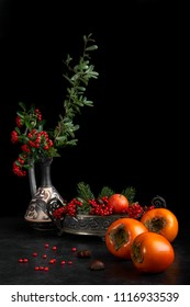 Still life with fall fruit as persimmon, chestnuts and mandarin orange, decorated with red berries.
