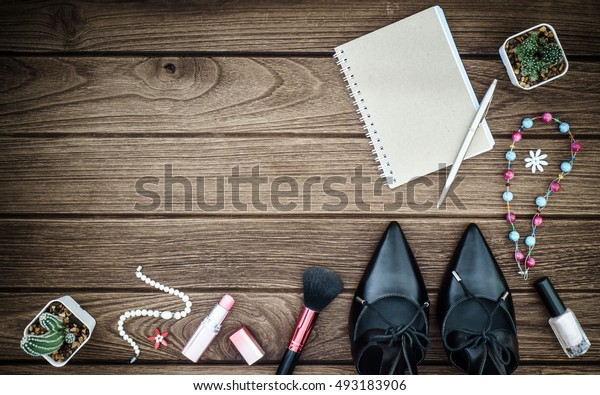 Still life of fashion woman. Feminine cosmetic background. Black patent leather shoes and blank notebook on the wooden floor.
