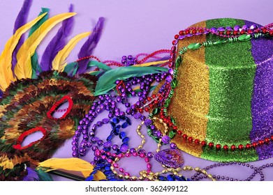 Still life with feathered mask, shiny party top hat, and beads on purple background. Objects symbolize Mardi Gras and also New Years, the opera, carnivals and the arts with copy space.