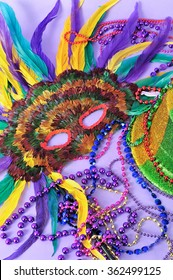 Still life with feathered mask, shiny party top hat,  beads on purple background. Objects symbolize Mardi Gras and also New Years, the opera, carnivals and the arts.