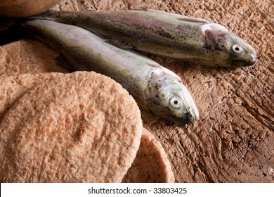 Still life of five loaves of bread and two fresh fish