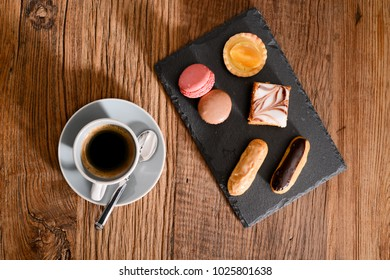 still life flat lay view with espresso coffee macaroons and french pastries on wooden rustic table