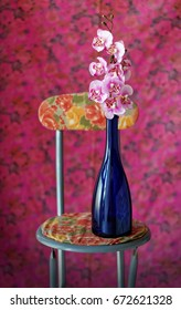 Still life with floral background with chair and a branch of fake orchids in a blue bottle