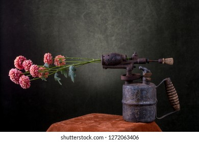 Still life with a flower branch and an old blowtorch