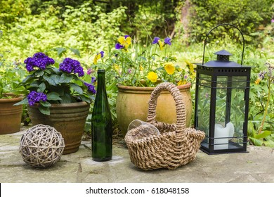 still life with flowers, basket, bottle, glasses and lantern in a garden