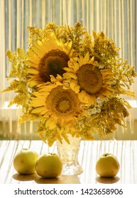Still life with flowers in glass vase and apples on wooden table. Sunflowers in a transparent glass vase in front of window light