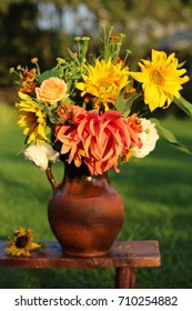 Still life with flowers in vintage clay pitcher on aged wooden stool in garden, evening light, real vertical photo