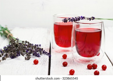 Still life, food and drink, health and homeopathy concept. Cranberry (red berries) drink in glass with lavender on a wooden table. Selective focus